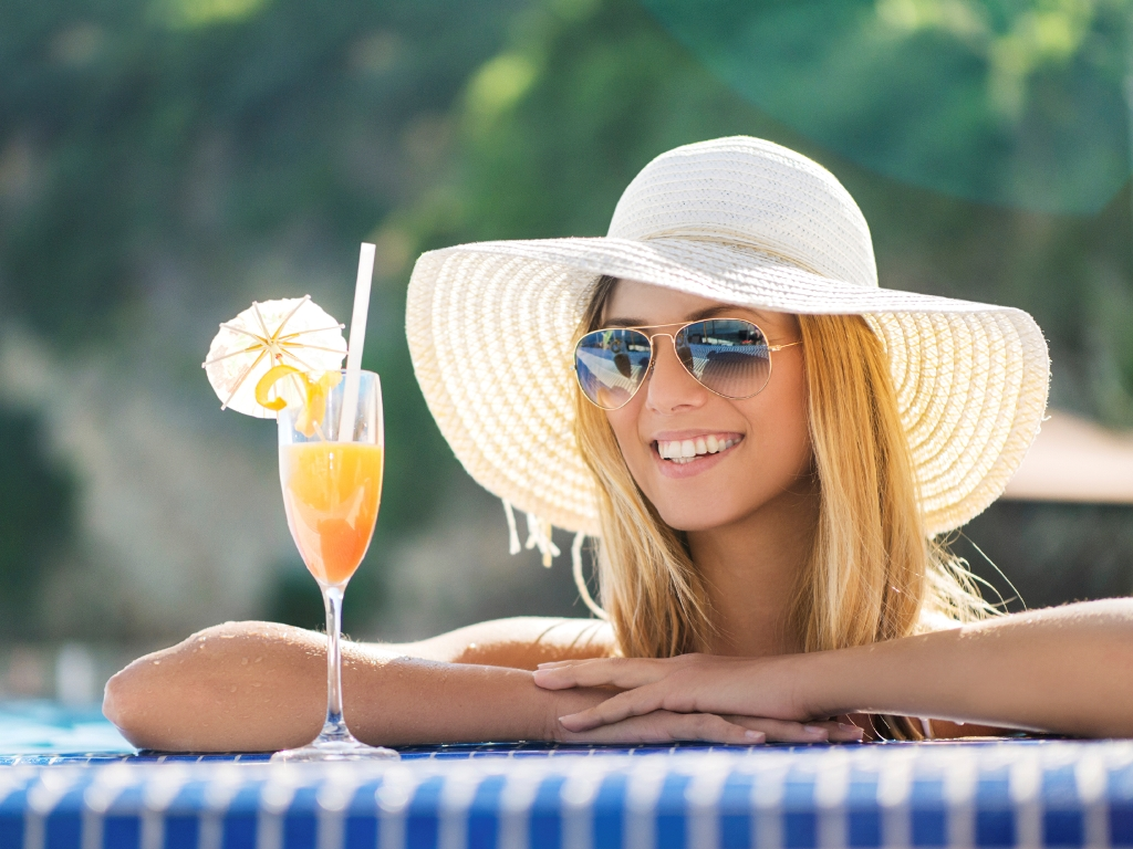 Beautiful woman with cocktail enjoying in summer day.